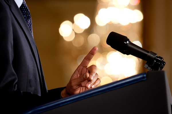 0519-0908-0820-3533_close_up_of_a_man_making_a_point_during_a_speech_microphone_and_podium_in_view_o1