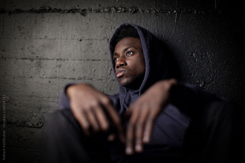 Sad black man in front of grunge wall