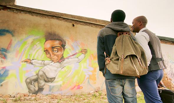 Reggie showing Diliza his graffiti art